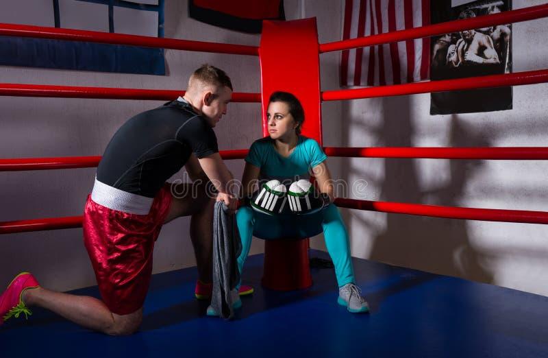Boxeador de sexo femenino joven en guantes de boxeo después de la batalla co siguiente que se sienta imágenes de archivo libres de regalías
