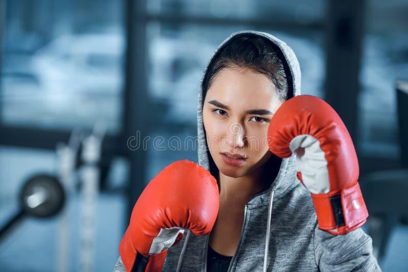 boxeador de sexo femenino joven en los guantes que miran la cámara fotos de archivo libres de regalías