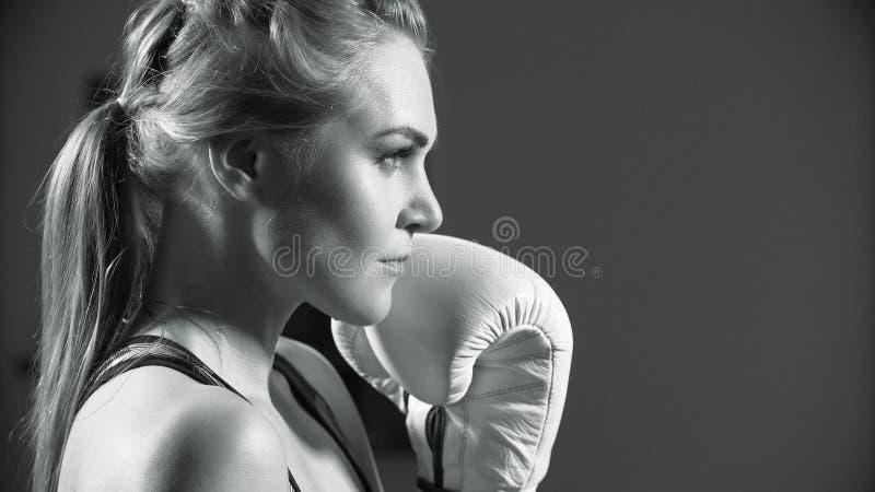 Boxeador de sexo femenino La mujer joven practica sus movimientos del boxeo Sacadores que lanzan del boxeador intenso de la mujer imagen de archivo