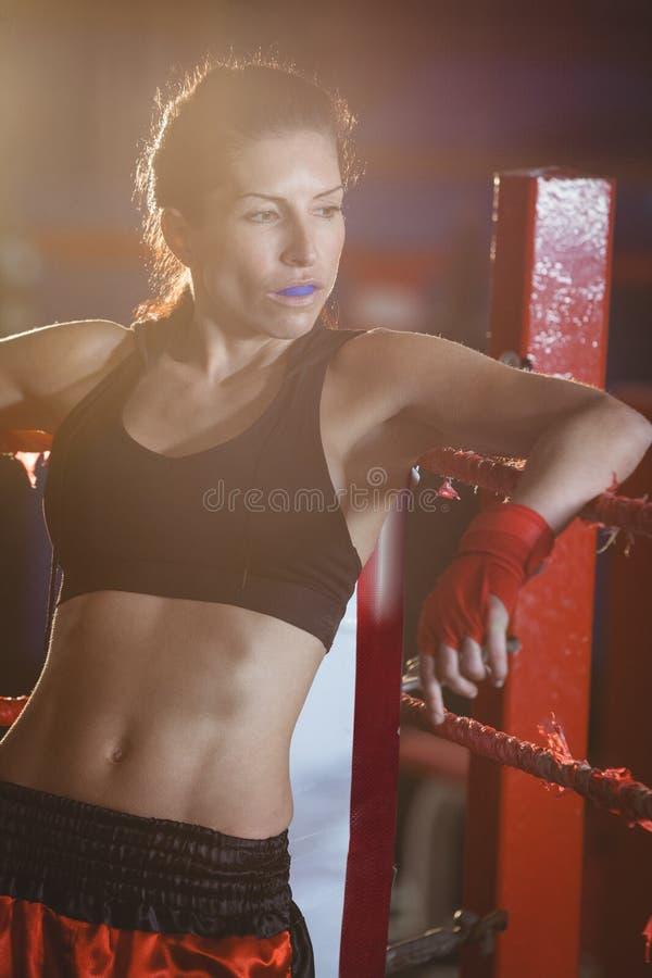 Boxeador de sexo femenino pensativo que se sienta en el anillo imágenes de archivo libres de regalías