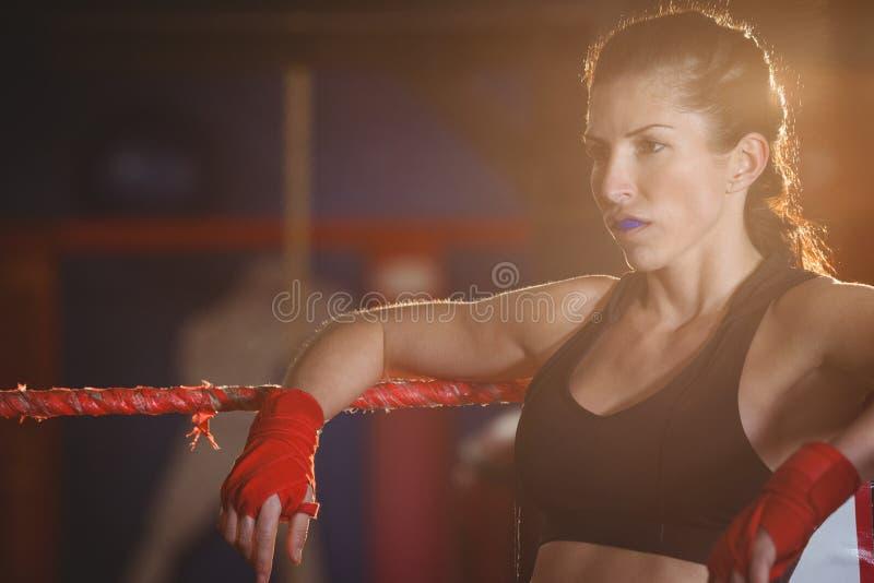 Boxeador de sexo femenino pensativo que se sienta en el anillo imagen de archivo libre de regalías