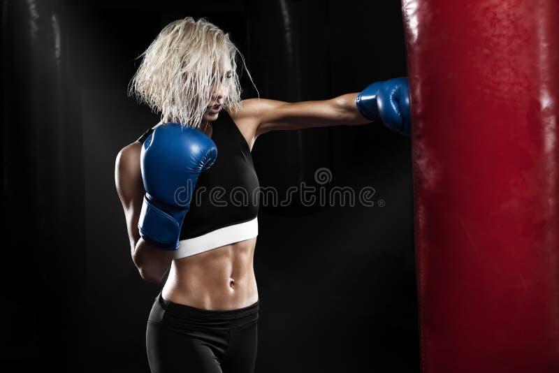 Boxeador de sexo femenino que golpea un saco de arena en un estudio de encajonamiento Entrenamiento del boxeador de la mujer fotografía de archivo libre de regalías