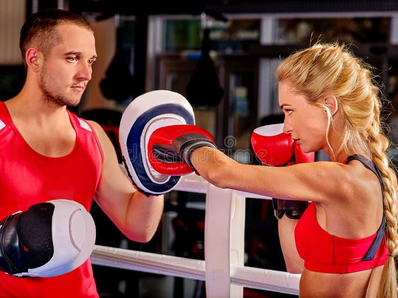 Boxeador de sexo femenino que lanza la cruz correcta en los mitones imagen de archivo