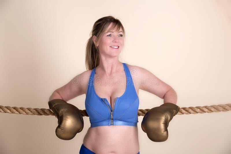 Boxeador de sexo femenino que lleva guantes de oro foto de archivo libre de regalías