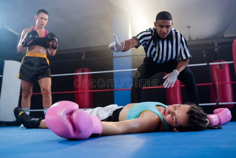 Boxeador de sexo femenino que mira mientras que árbitro que cuenta por el atleta imágenes de archivo libres de regalías