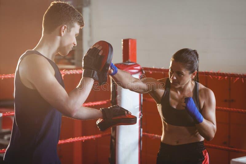 Boxeador de sexo femenino que practica con el instructor en el anillo imágenes de archivo libres de regalías