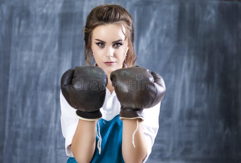 Boxeador de sexo femenino que presenta en los guantes de cuero del boxeador de Brown contra Blacboard foto de archivo