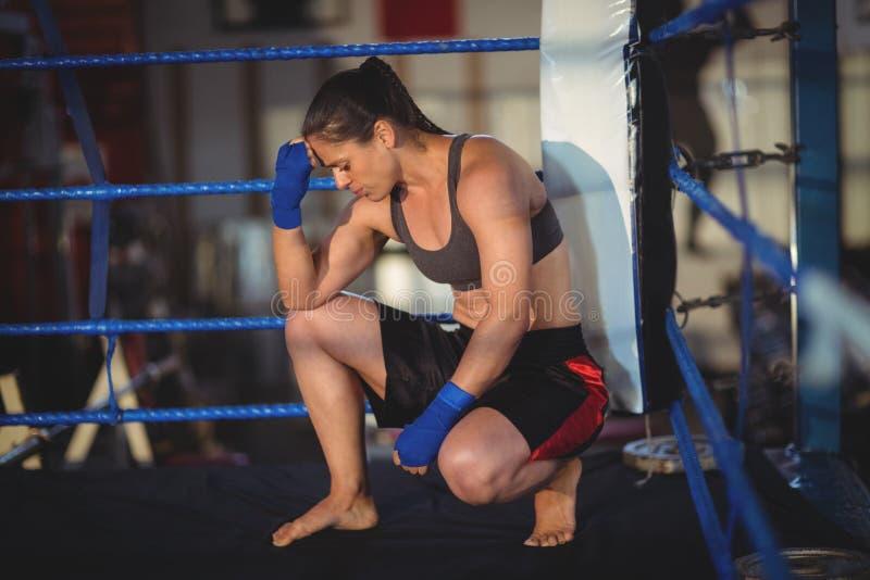 Boxeador de sexo femenino que se agacha en ring de boxeo foto de archivo