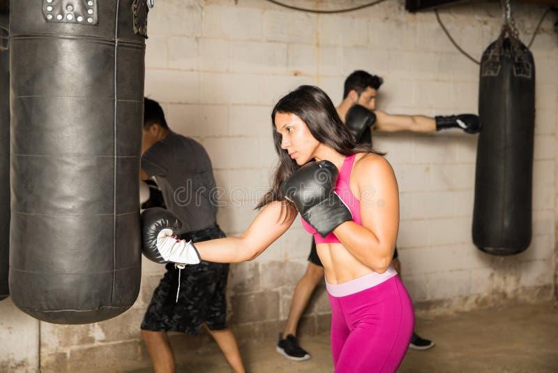 Boxeador de sexo femenino que trabaja en su técnica fotos de archivo