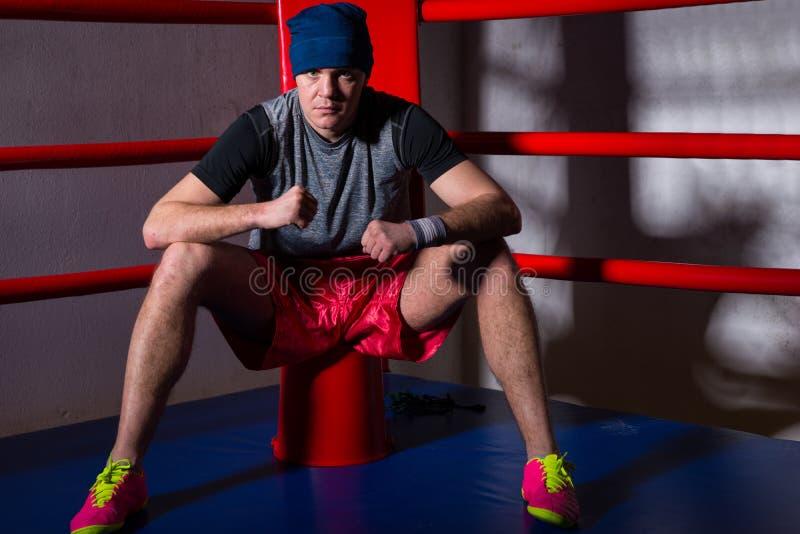 Boxeador de sexo masculino atlético que se sienta cerca de esquina roja de un boxeo regular imagen de archivo