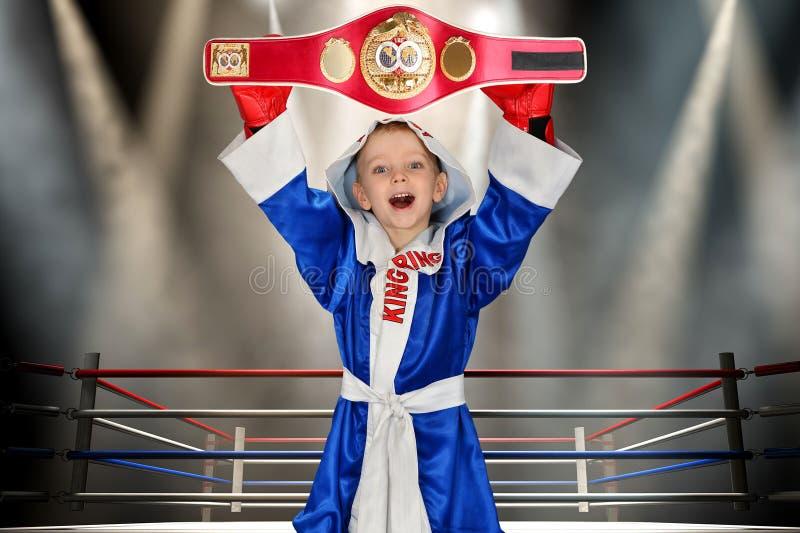 Boxeador del muchacho que sostiene la correa del campeonato en el boxeo Pequeño campeón Los triunfos grandes fotos de archivo