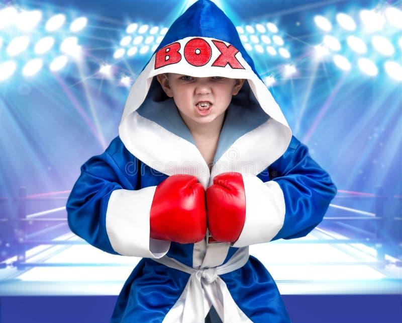 Boxeador del niño pequeño con los guantes rojos y traje en el fondo del anillo Pequeño campeón Los triunfos grandes fotos de archivo libres de regalías