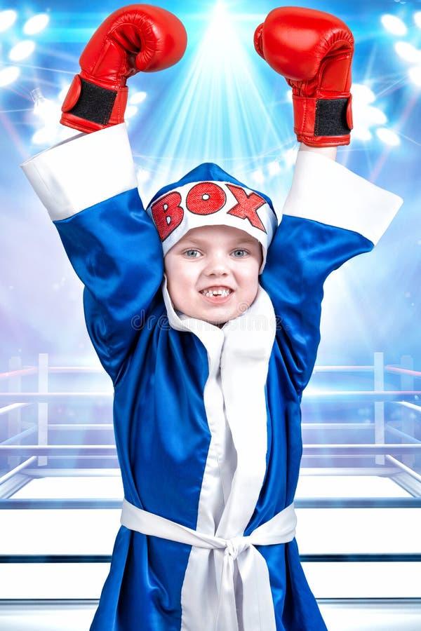Boxeador del niño pequeño con los guantes rojos y traje en el fondo del anillo Pequeño campeón Los triunfos grandes imagenes de archivo