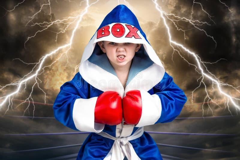 Boxeador del niño pequeño con los guantes y el traje rojos Pequeño campeón Los triunfos grandes imagen de archivo libre de regalías