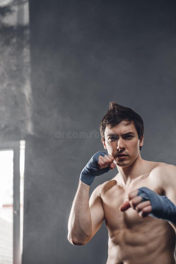 Boxeador fuerte en los rayos de las manos del entrenamiento del sol y del humo con los abrigos del boxeo foto de archivo