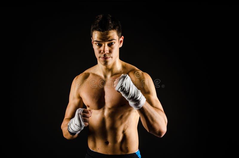 Boxeador fuerte joven con los abrigos de la mano imagen de archivo