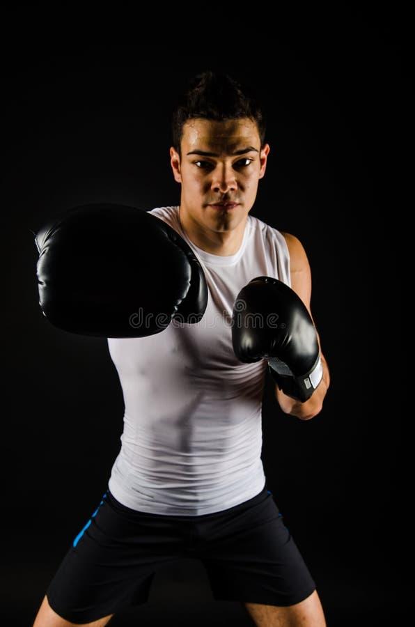 Boxeador fuerte joven con los guantes negros fotos de archivo libres de regalías