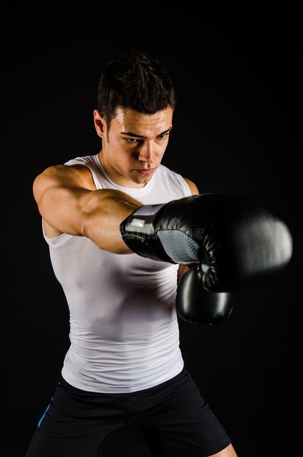 Boxeador fuerte joven con los guantes negros imágenes de archivo libres de regalías