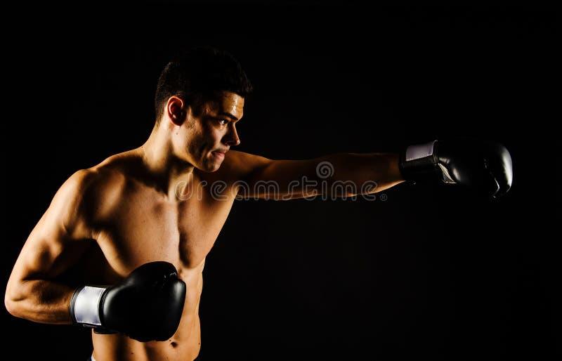 Boxeador fuerte joven con los guantes negros fotos de archivo