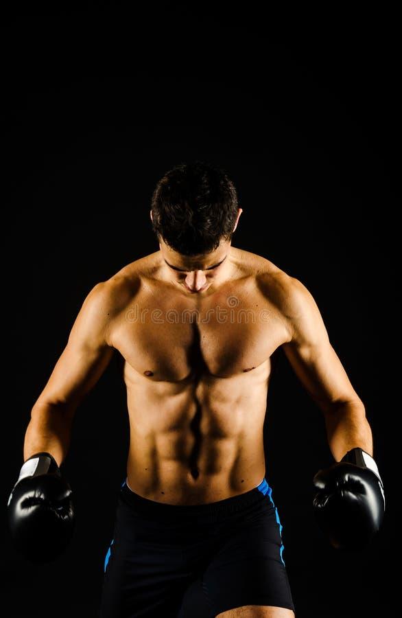 Boxeador fuerte joven con los guantes negros foto de archivo