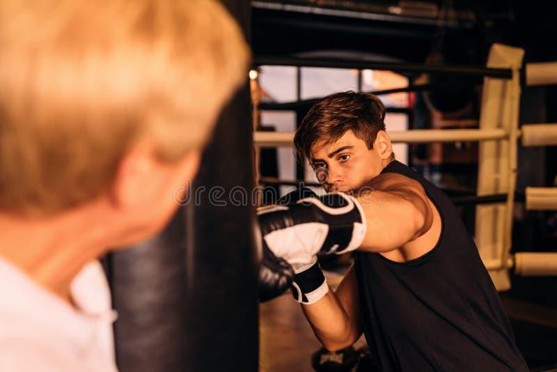 Boxeador joven que golpea un saco de arena imagenes de archivo