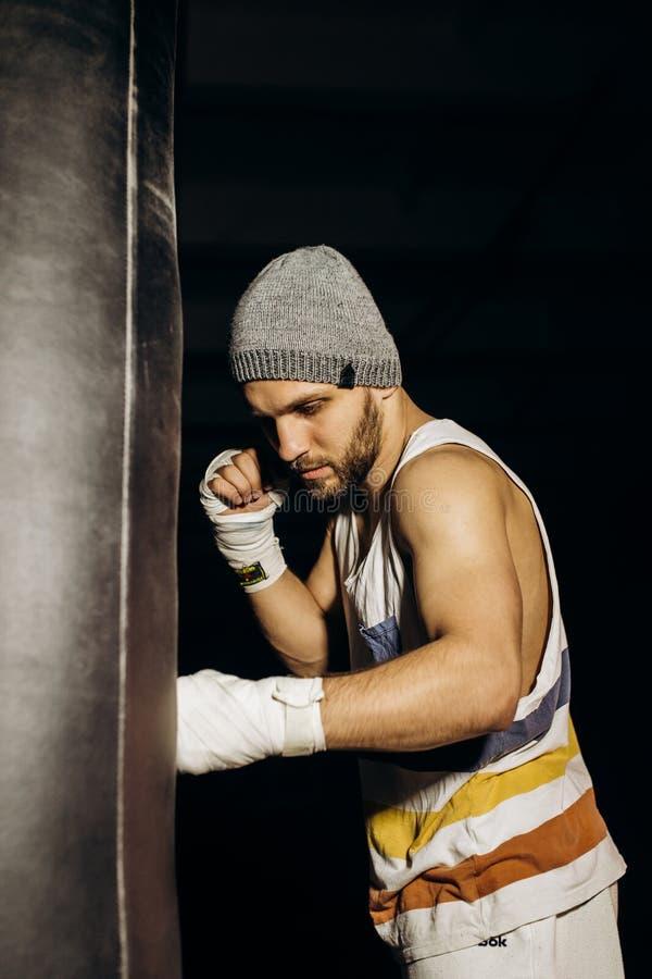Boxeador joven que lucha con los puños vendados imagenes de archivo