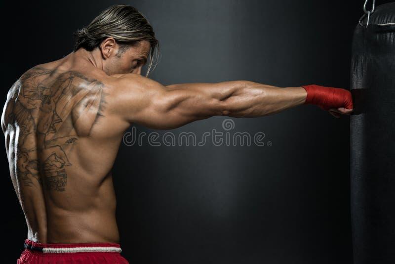 Boxeador muscular descamisado con el saco de arena en gimnasio foto de archivo