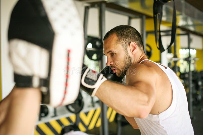 Boxeador que golpea el guante de su compañero de entrenamiento fotos de archivo libres de regalías