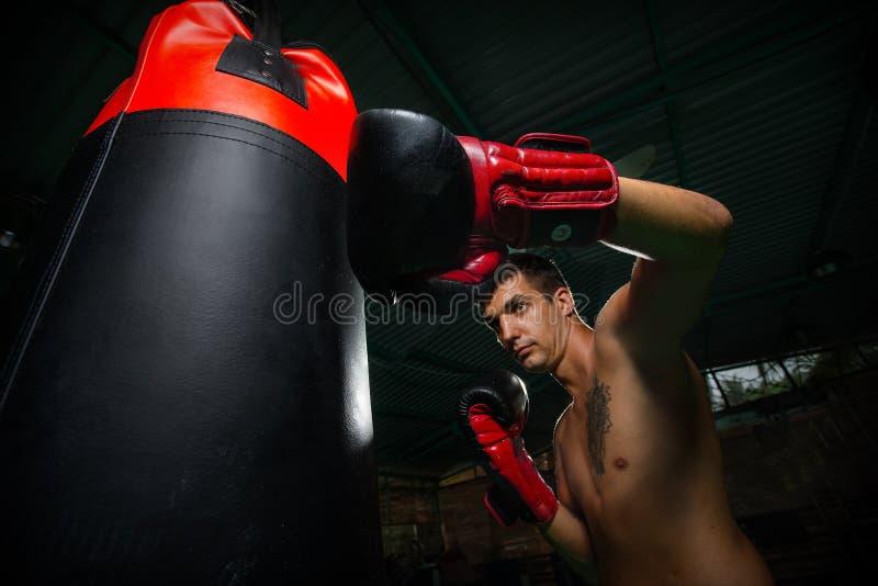 Boxeador que golpea la bolsa de arena con el pie fotos de archivo