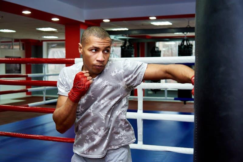 Boxeador que golpea un saco de arena enorme en un estudio de encajonamiento Boxeador que entrena difícilmente fotografía de archivo libre de regalías