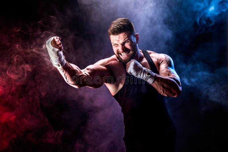 Boxeador tailandés muay del deportista que lucha en fondo negro con humo foto de archivo