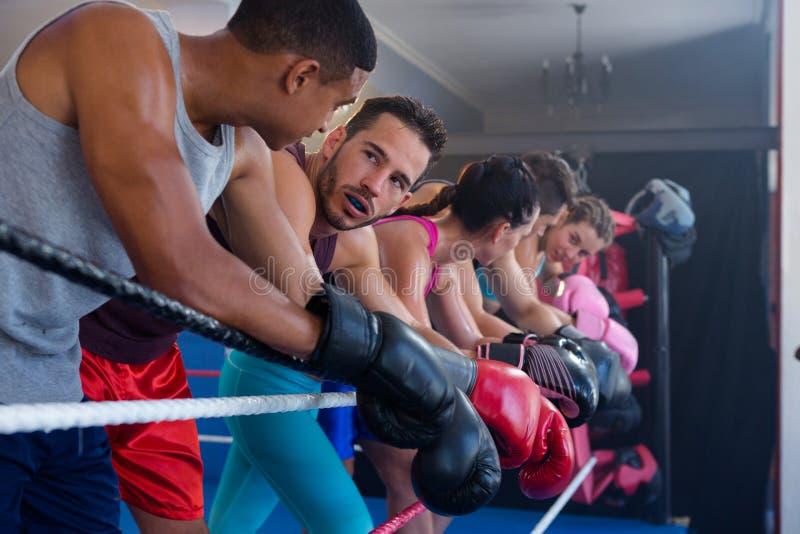 Boxeadores de sexo masculino y de sexo femenino cansados que se inclinan en cuerda fotos de archivo libres de regalías