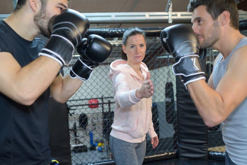 2 boxeadores que esperan al coche femenino para comenzar lucha fotografía de archivo libre de regalías