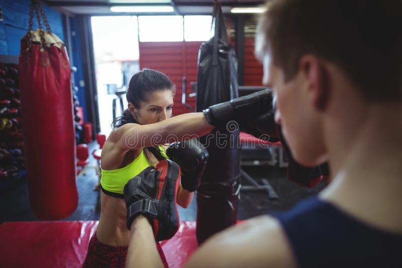 Boxeadores que usan los mitones del foco durante el entrenamiento imagen de archivo
