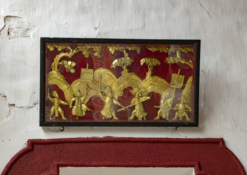 Boxed gold relief of soldiers at war, Cantonese Assembly Hall in Hoi An. Pictured is a boxed gold relief of ancient Chinese soldiers at war in the Cantonese stock photos