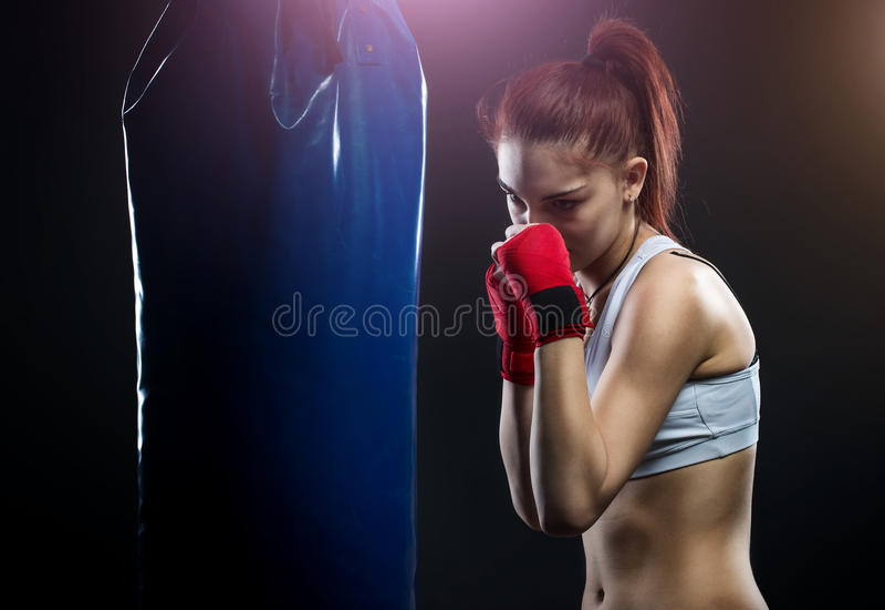 Boxeo de la mujer joven en un saco de arena fotos de archivo