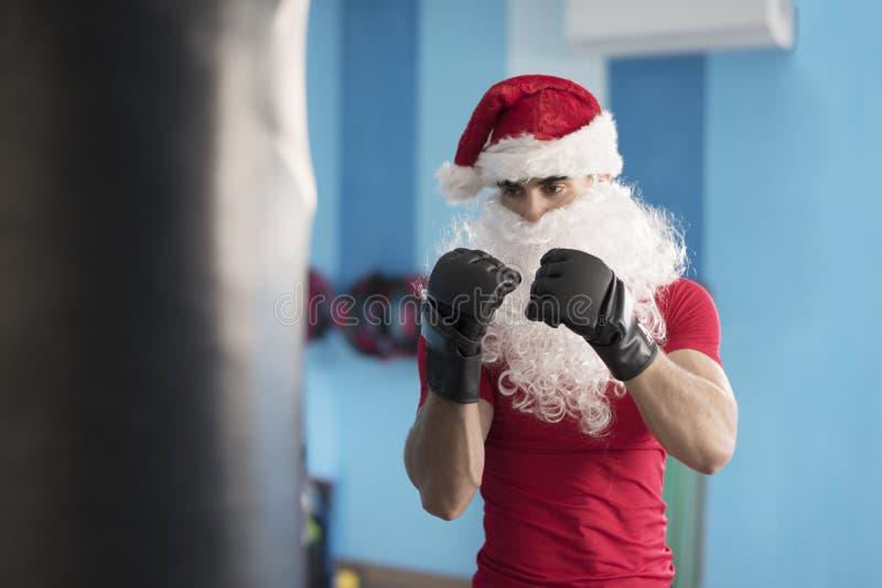 Boxeo de Papá Noel de la aptitud contra rea gordo del bolso de los días de fiesta de la Navidad fotos de archivo