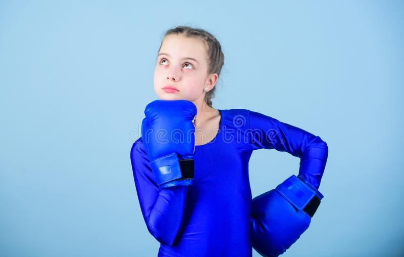 Boxer child in boxing gloves. Female boxer change attitudes within sport. Rise of women boxers. Girl cute boxer on blue. Boxer child in boxing gloves. Female stock photography