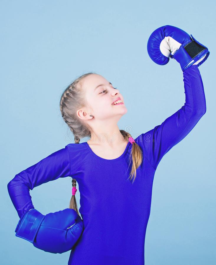 Boxer child in boxing gloves. Rise of women boxers. Female boxer change attitudes within sport. Free and confident. Girl. Cute boxer on blue background. With royalty free stock photos