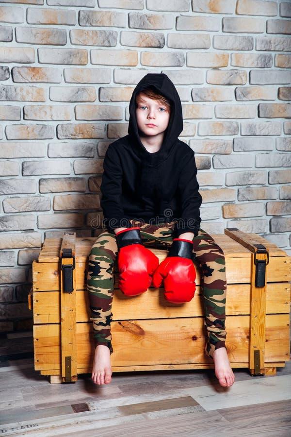 Boxer des kleinen Jungen mit Behandlung des blonden Haares in den tragenden Boxhandschuhen des schwarzen Sweatshirts, die in eine stockbilder