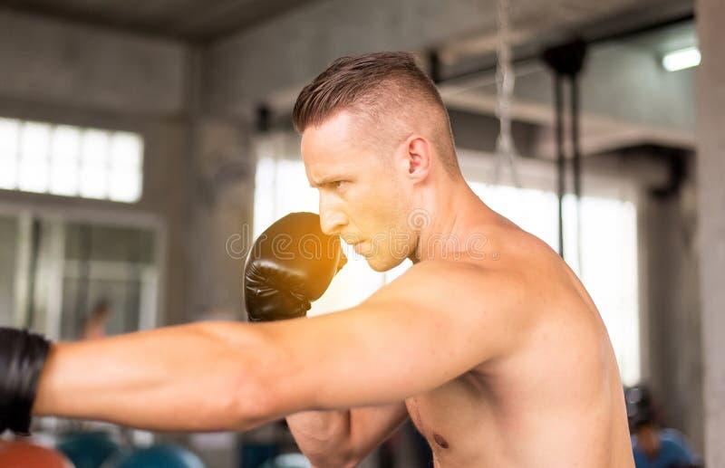 Boxer des Sportgut aussehenden mannes, der an einer boxenden Turnhalle, Mannboxerauge schaut locht, ausbildend auf Sandsack lizenzfreie stockfotos
