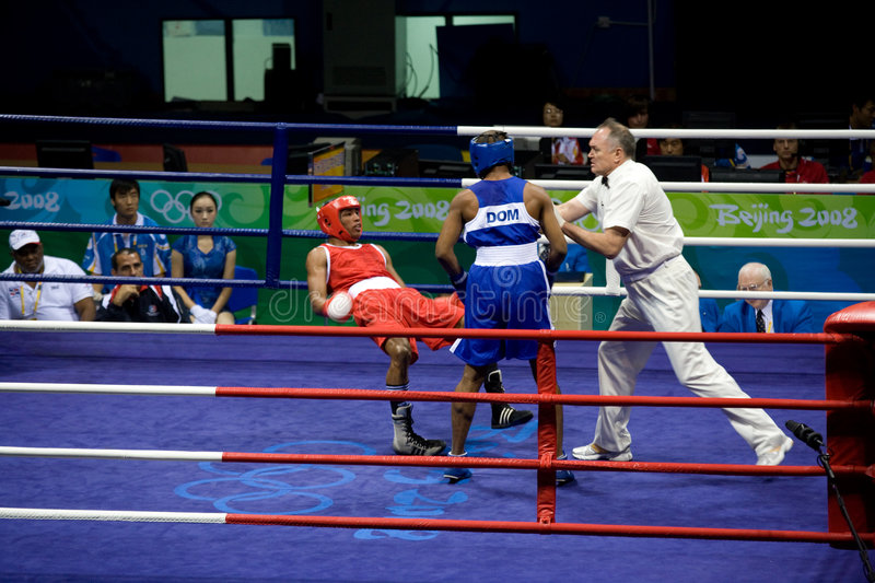 Boxer falls during Olympic bout. Boxer Alfonso Blanco Parra of Venezuela falls after a punch from Argenis Nunez of the Dominican Republic during Olympics in royalty free stock photography