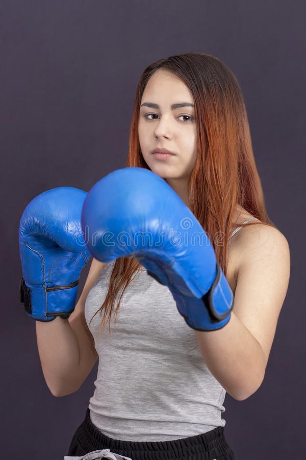Boxer girl in blue boxing gloves in a gray t-shirt in rack royalty free stock photos