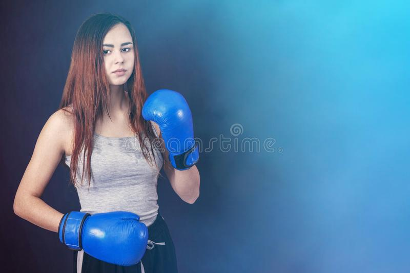 Boxer girl in blue boxing gloves in a gray t-shirt in the rack on a gray background. Copyspace royalty free stock photos