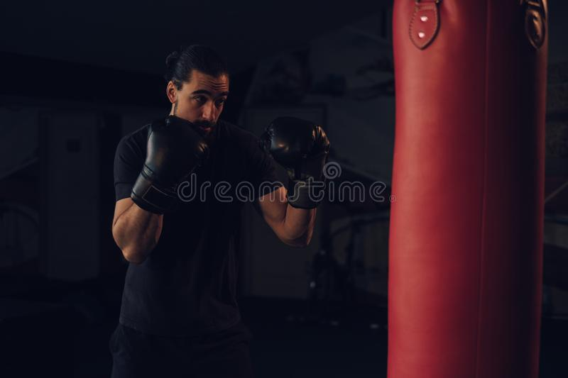Boxer in guard in front of the heavy bag royalty free stock photos