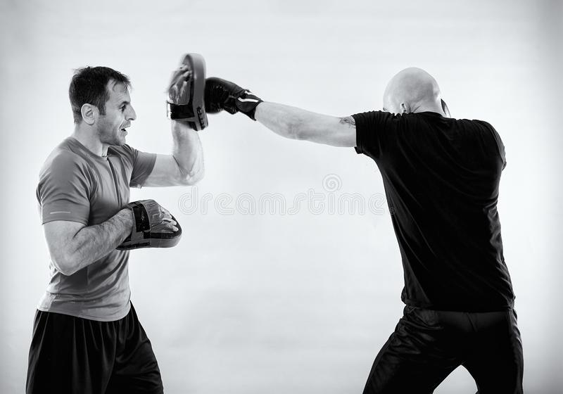 Black and white of boxer with trainer. Boxer and his coach hitting mitts, black and white image stock photography