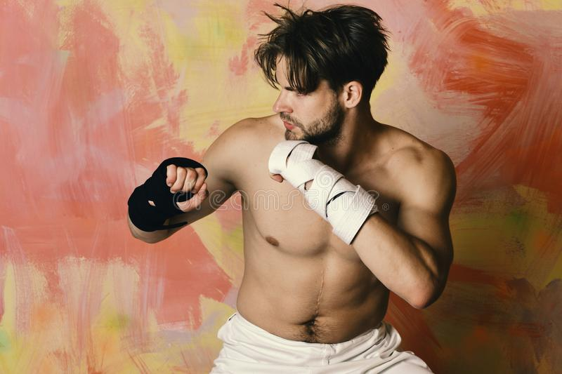 Boxer or karate fighter practices martial arts. Man with busy face and naked torso on colorful background. Japanese karate training and sports concept. Guy stock image