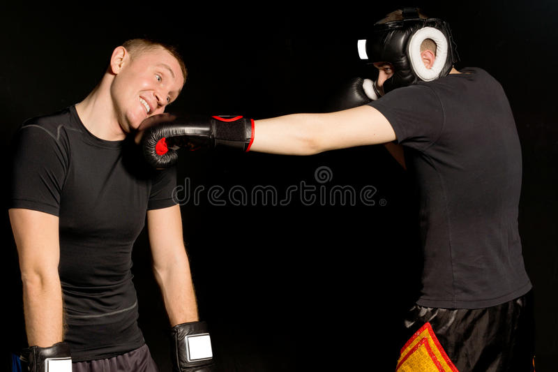 Boxer landing a punch on his opponents jaw. As the two men fight it out in the ring during a match on a dark background royalty free stock photography