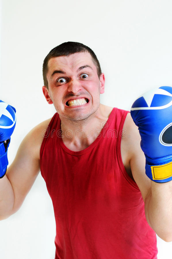 Boxer man with boxing gloves. Young handsome male athlete with boxing gloves, boxer working out, fitness Studio shot. Evil boxer. Man`s face stock image