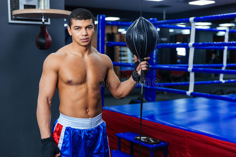 Boxer standing in gym and looking at camera. Handsome male boxer standing in gym and looking at camera stock photography